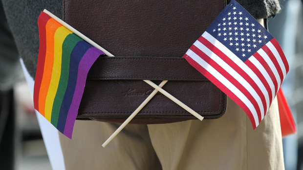 SAN FRANCISCO, CA - JUNE 13:  A gay pride and an American flag hang from a shoulder bag during a demonstration outside of the Phillip Burton Federal Building on June 13, 2011 in San Francisco, California.  Sponsors of Proposition 8, a California ballot measure that would deny same-sex couples to marry in the state, are back in court today to ask a federal judge to nullify U.S. District Judge Vaughn Walker's decision to overturn California's ban on same-sex marriage. (Photo by Justin Sullivan/Getty Images)